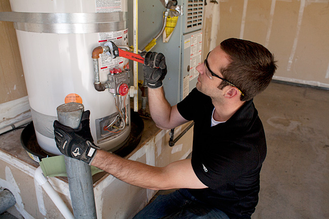 plumber in Tacoma repairs an American Standard water heater in a garage